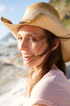 relaxing beach: Close up portrait of an attractive woman smiling with hat at the beach Stock Photo