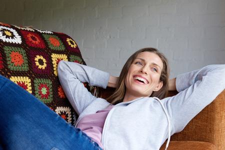 ソファで横になっている笑顔の年上の女性の肖像画