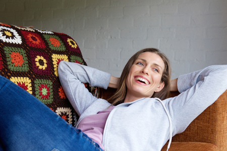 woman lying down: Portrait of a smiling older woman lying down on couch