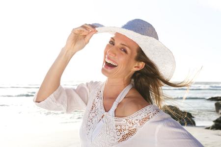 해변에서 모자와 함께 웃 고있는 매력적인 여자의 초상화를 닫습니다