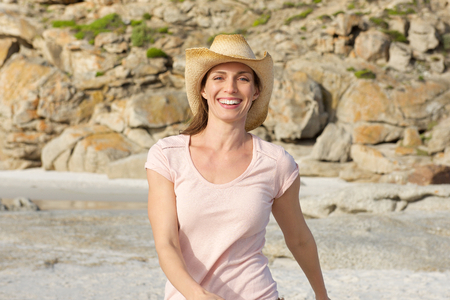 Portrait of a smiling older woman walking at the beach with hat