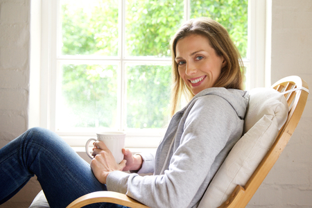 woman chair: Side portrait of a smiling older woman relaxing at home with cup of tea