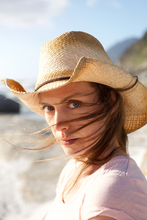 beautiful eyes: Close up portrait of a woman with hat and hair blowing in face Stock Photo