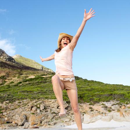 cheerful woman: Retrato de una mujer feliz saltando al aire libre