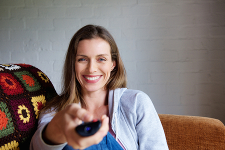 one woman: Portrait of an attractive woman smiling with TV remote control Stock Photo