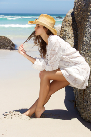 barefoot cowboy: Full length side portrait of a beautiful young woman leaning against rock at the beach Stock Photo
