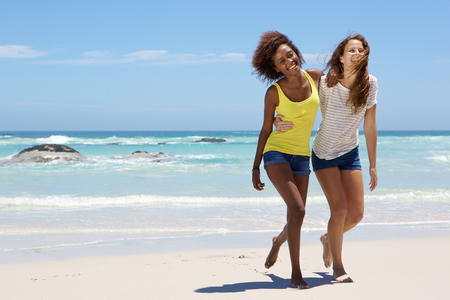woman barefoot: Full length portrait of two girl friends walking on the beach