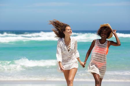 mujeres juntas: Retrato de dos mujeres sonrientes caminando juntos en la playa