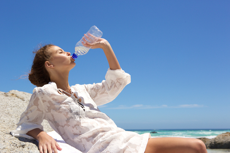 water bottle: Side portrait of a young woman drinking water from bottle at the beach Stock Photo
