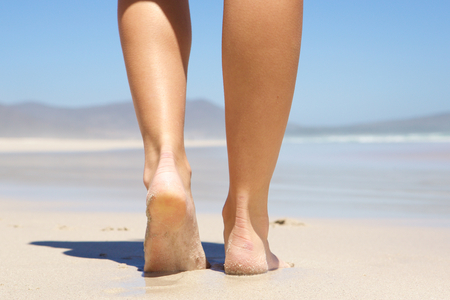 in behind: Low angle woman walking barefoot on beach from behind