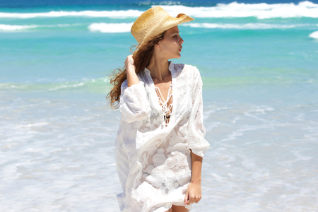 white hat: Portrait of a beautiful young woman with hat at the beach