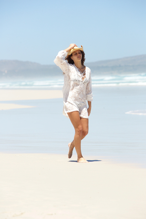 one woman: Beautiful woman walking carefree on secluded beach Stock Photo