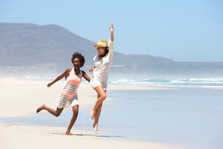 pies descalzos: Retrato de cuerpo entero de dos mujeres jóvenes despreocupados caminar descalzo en la playa Foto de archivo