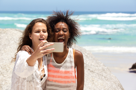 woman beach: Portrait of two happy young women taking selfie at the beach