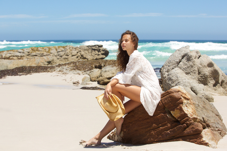 young girl barefoot: Full length portrait of a young woman sitting on rock at the beach Stock Photo