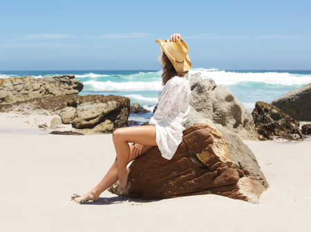 barefoot cowboy: Portrait of a woman sitting on beach looking at the sea Stock Photo