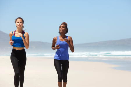 mujeres corriendo: Portrait of two female runners exercising on the beach