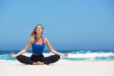 relaxing beach: Healthy young yoga woman sitting in lotus pose at the beach
