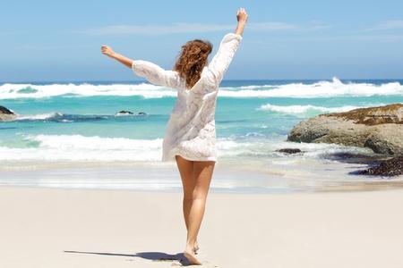 Detrás de la mujer joven con los brazos levantados en el aire en la playa Foto de archivo - 51988408