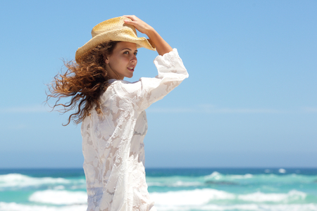 one person: Portrait of a fashion model with white summer dress and hat posing at the beach