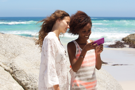 modelos negras: Portrait of two female friends at the beach looking at mobile phone together