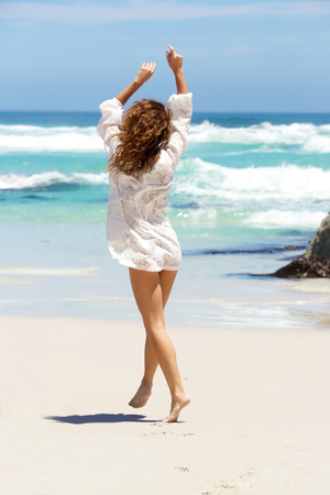Full body portrait of a carefree young woman in summer dress walking to water on beach