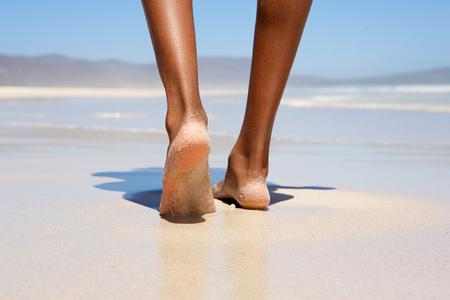 pies: Mujer bajo ángulo de caminar descalzo en la playa