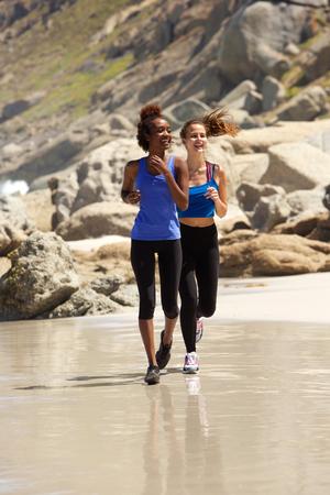 outdoor exercise: Full length young women enjoying run on beach