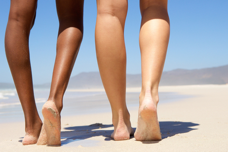 woman foot: Low angle two women walking barefoot on beach Stock Photo