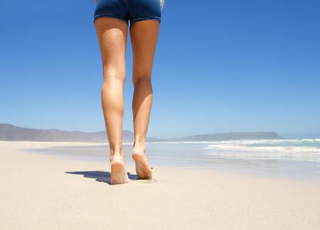 pies descalzos: Piernas femeninas caminar descalzo en la playa desde atr�s