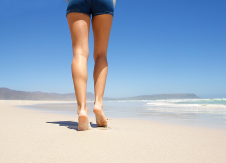 Female legs walking barefoot on beach from behind