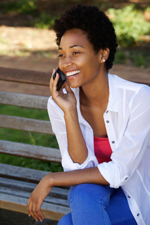 outdoors woman: Close up portrait of happy young african american woman sitting on a park bench talking on mobile phone