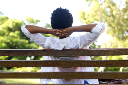hands behind head: Rear portrait of young woman relaxing on park bench with hands behind head Stock Photo