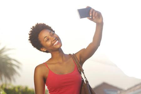 Close-up portret van een aantrekkelijke jonge Afro-Amerikaanse vrouw die een selfie met haar mobiele telefoon