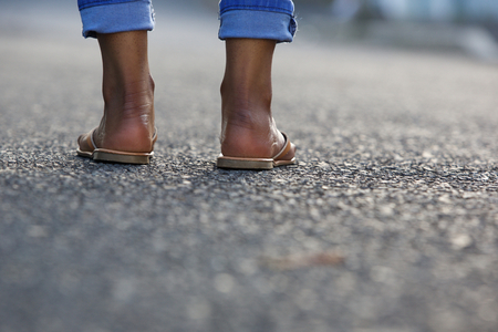 angle: Close up portrait of a young woman legs standing on city street