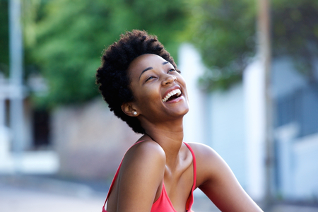 mujer sola: Close up portrait of cheerful young african woman sitting outdoors and laughing