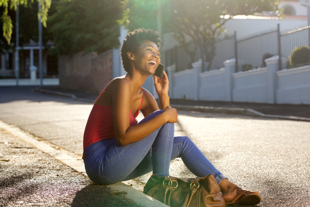 Portrait of young woman sitting along a street and talking on mobile phone on a summer day Stock Photo