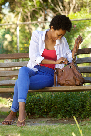 woman searching: Portrait of young african woman sitting on park bench looking into her bag Stock Photo