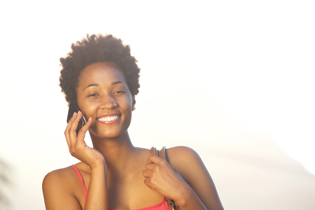 black lady: Close up portrait of a beautiful young african woman talking on mobile phone