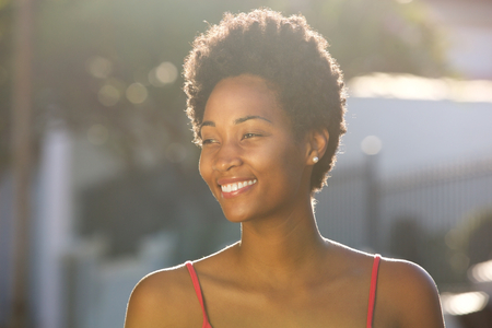 natural light: Close up portrait of happy young african woman smiling outdoors