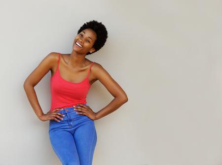 hair curly: Retrato de mujer joven con estilo de pie con las manos en las caderas mientras está de pie contra una pared