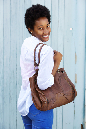 woman bag: Portrait of an attractive young woman standing against a wall carrying a purse and looking over her shoulder