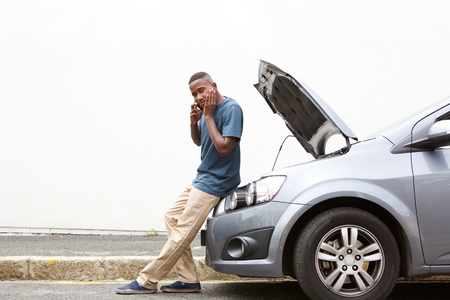 call for help: Full length portrait of upset young african man standing in front of a broken car and making a phone call for help