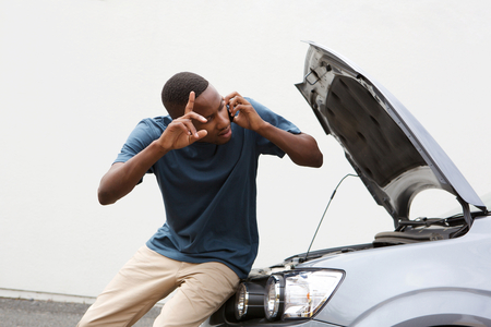call for help: Portrait of young african guy standing in front of a broken car and making a phone call for help