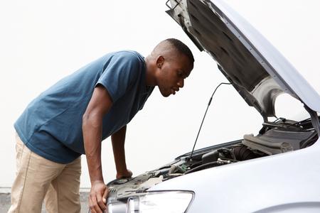 壊れた車のボンネットの下を探して若いアフリカ系アメリカ人男の側の肖像 写真素材