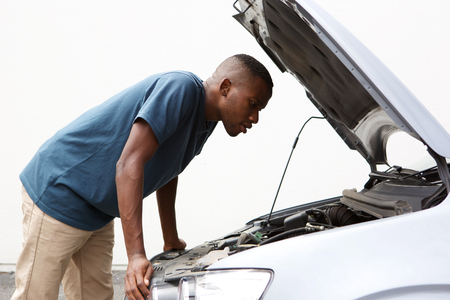 Side portrait of young african american guy looking under the hood of broken down car