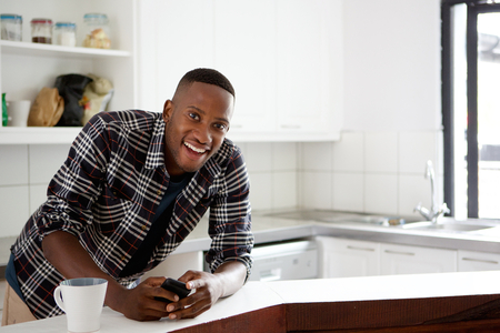 happy african: Portrait of happy young african man standing in the kitchen holding mobile phone and cup of coffee on counter