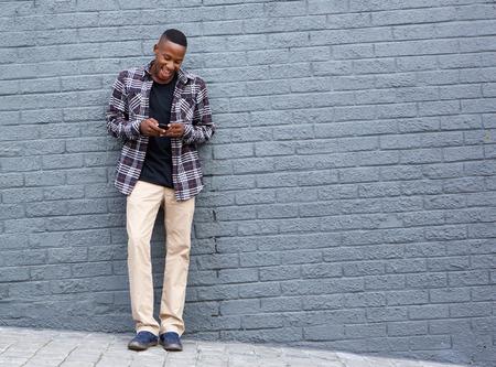 hombres negros: retrato de cuerpo entero del hombre joven y fresco de pie contra una pared gris y lectura de mensajes de texto en su celular