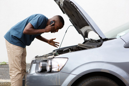 Side portrait of a young african man having trouble with his broken car calling for help on cell phone.