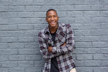 Portret van een gelukkig African American man lachend met de armen gekruist